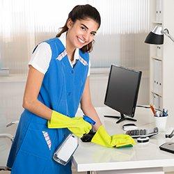 kobieta czyści blat biurka