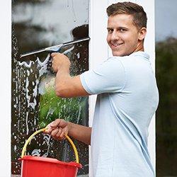 mężczyzna myje okno